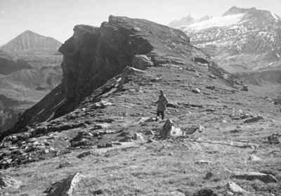 A surveyor in front of a rock