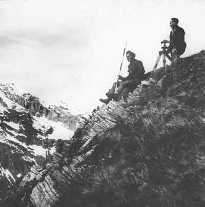 Two surveyors sitting on a rock