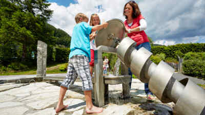 Children with woman trying on the Archimedes' screw located