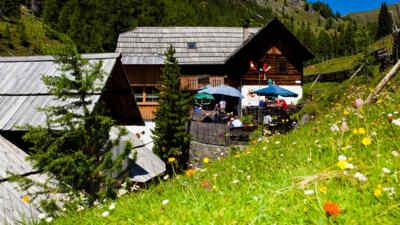 Touristen sitzen bei einer Hütte